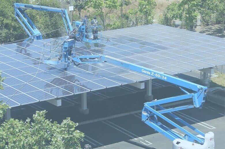Grúa limpiando una instalacion de paneles solares